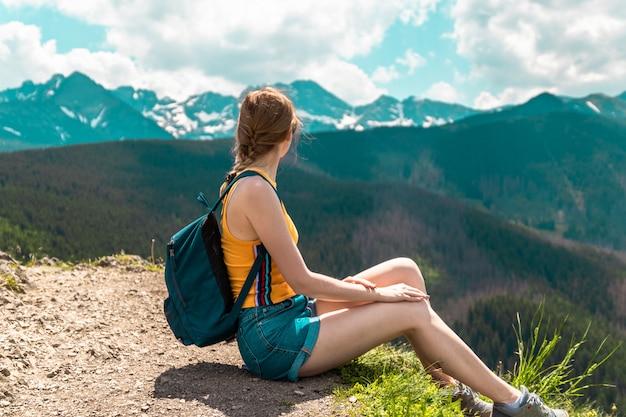 Linda chica rubia con una mochila y gafas se sienta en una montaña y disfruta de las hermosas colinas de las montañas en un día soleado. Foto Premium