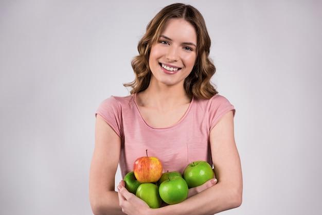 Linda chica sonríe y sostiene deliciosas manzanas en sus manos. Foto Premium