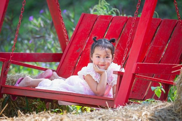 Linda chica sonriendo felizmente con un hermoso vestido rosa. Foto gratis