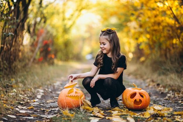 Linda chica vestida con disfraz de halloween al aire libre con calabazas Foto gratis