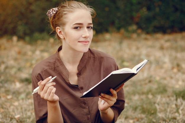 Linda estudiante que trabaja en un parque y usa el cuaderno Foto gratis