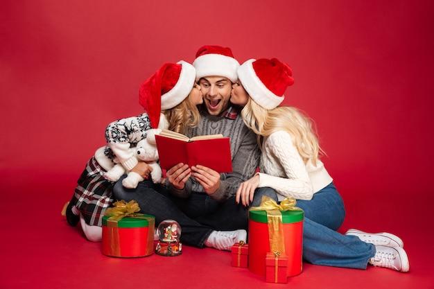 Linda familia joven con sombreros de navidad Foto gratis