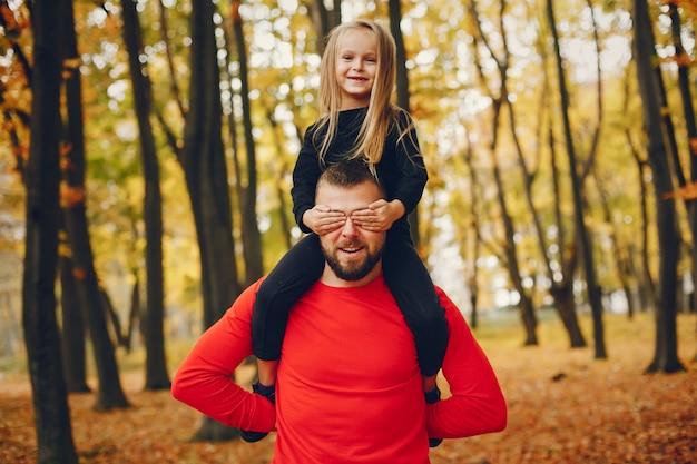 Linda familia jugando en un parque de otoño Foto gratis