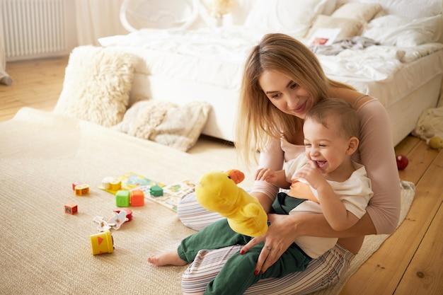 Linda hermana pasar tiempo con su hermanito, sentada en el suelo en el dormitorio. hermosa niñera joven jugando con el niño en el interior, sosteniendo un pato de peluche. infancia, puericultura y maternidad Foto gratis