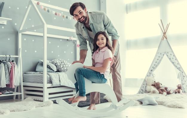 Linda hija y su joven padre están mirando a cámara. Foto Premium