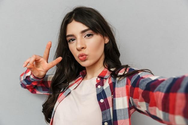 Linda jovencita hermosa hacer selfie mirando la cámara hacer gesto de paz. Foto Premium