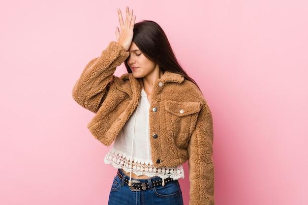 Linda jovencita olvidando algo, golpeándose la frente con la palma y cerrando los ojos. Foto Premium