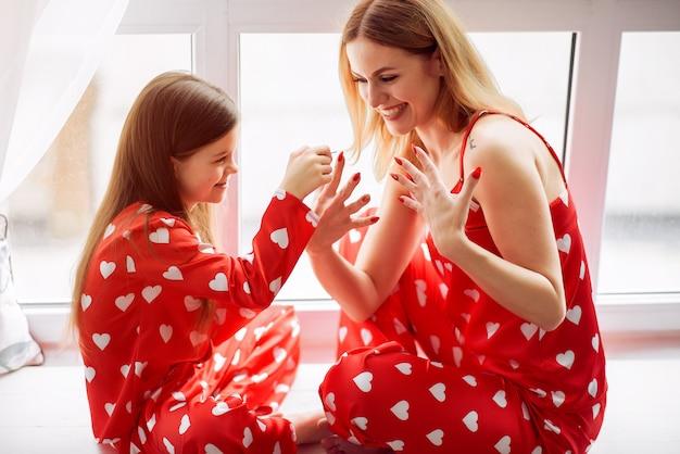 Linda madre e hija en casa en pijama Foto gratis