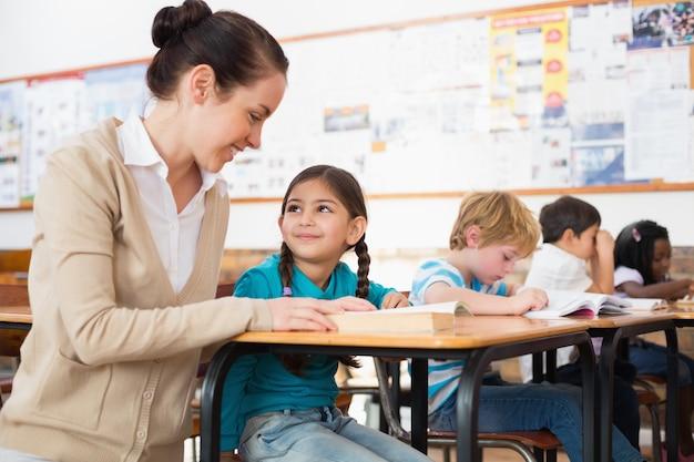 Linda maestra ayudando a los alumnos en el aula Foto Premium