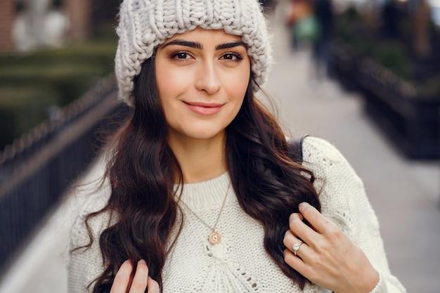 Linda morena en un suéter blanco en una ciudad Foto gratis
