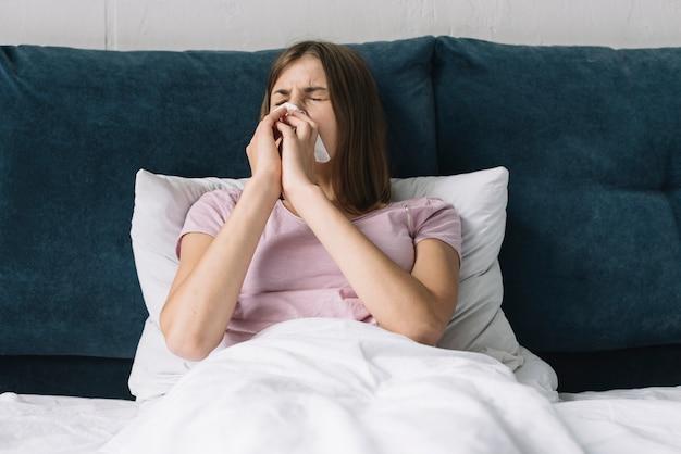 Linda mujer acostada en cama sufriendo de frío Foto gratis