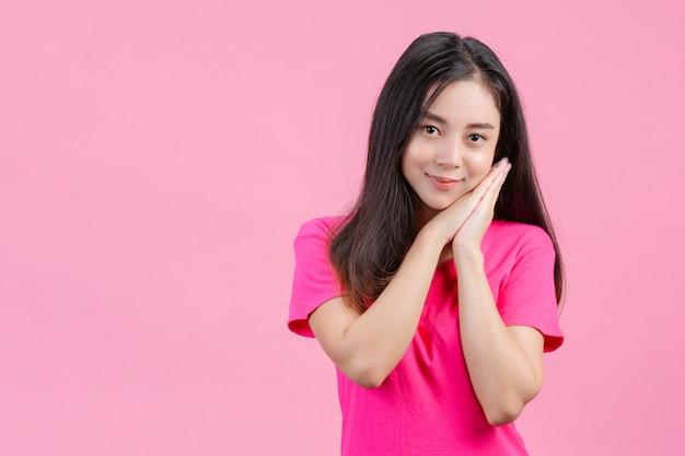 Linda mujer asiática blanca plantea tímido en un rosa. Foto gratis