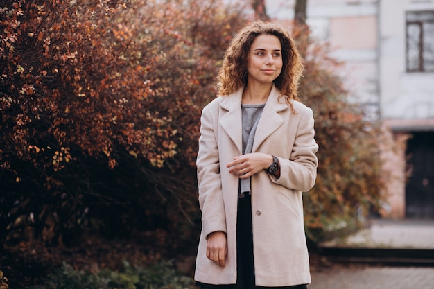 Linda mujer con cabello rizado caminando en un abrigo de otoño Foto gratis