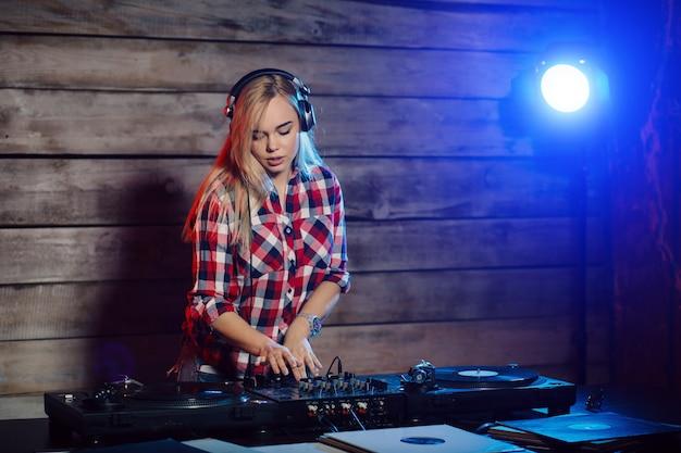 Linda mujer dj divirtiéndose tocando música en la fiesta del club Foto gratis
