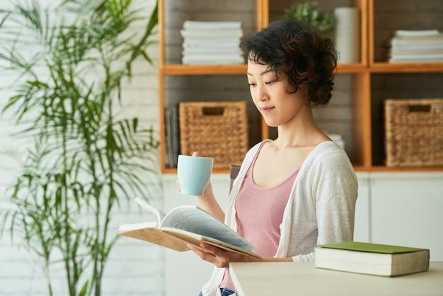 Linda mujer envuelta en lectura Foto gratis