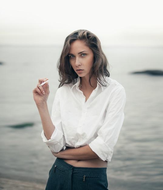 Linda mujer fuma un cigarrillo en la playa Foto Premium