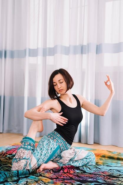 Linda mujer haciendo yoga con gesto mudra en el gimnasio Foto gratis