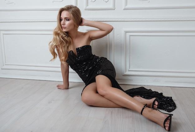 Linda mujer rubia en un hermoso vestido negro Foto Premium