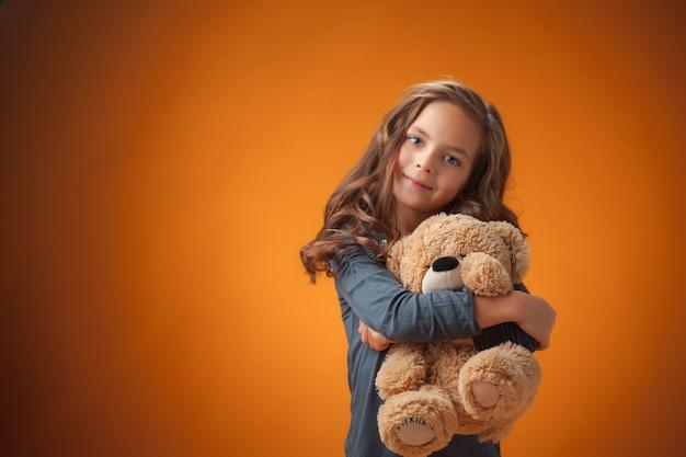 La linda niña alegre sobre fondo naranja Foto gratis