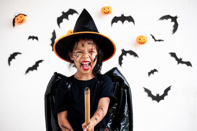 Linda niña asiática con disfraces de halloween y maquillaje divirtiéndose en la celebración de halloween Foto Premium