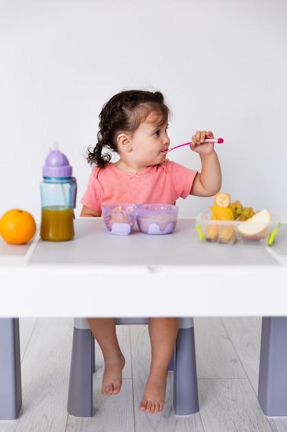 Linda niña comiendo frutas y bebiendo jugo Foto gratis