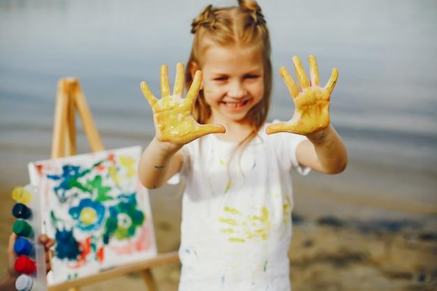Linda niña pintando en un parque Foto gratis