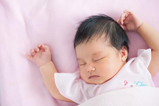 d484932d8 Linda niña recién nacida asiática durmiendo en la cama con una manta rosa  Foto Premium