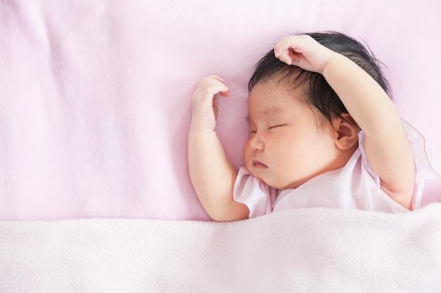 082c06e8f Linda niña recién nacida asiática durmiendo en la cama con una manta rosa
