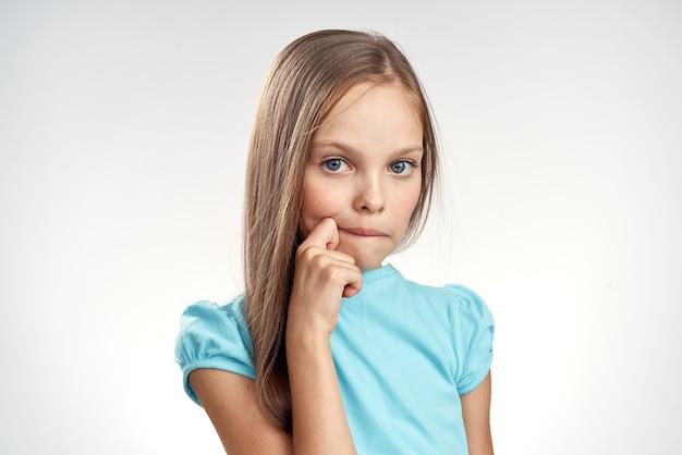 Linda niña vestidos azules vista recortada fondo claro emociones infancia diversión Foto Premium