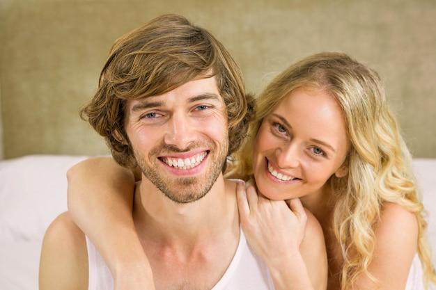 Linda pareja abrazándose en su cama en el dormitorio Foto Premium