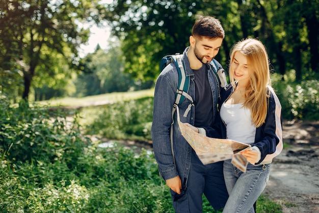 Linda pareja descansa en un bosque de verano Foto gratis