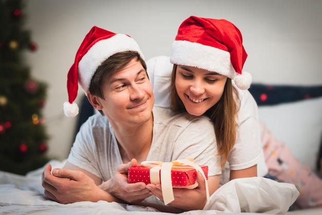 Linda pareja en dormitorio con regalo Foto gratis