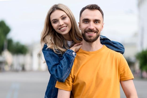 Linda pareja joven sonríe a la cámara Foto gratis