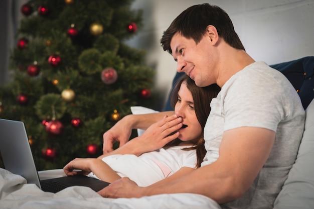 Linda pareja mirando portátil en la cama Foto gratis