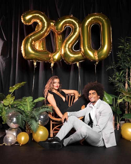 Linda pareja rodeada de globos con 2020 año nuevo Foto gratis
