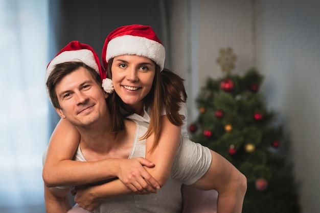 Linda pareja con sombreros de santa Foto gratis