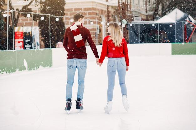 Linda pareja en un suéter rojo divirtiéndose en una arena de hielo Foto gratis
