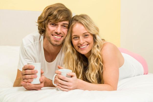 Linda pareja tomando un café acostado en su cama Foto Premium
