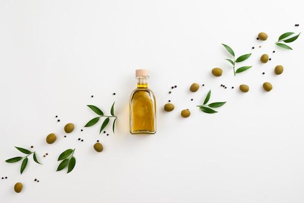 Lindo arreglo de hojas y aceite de oliva sobre fondo blanco. Foto gratis