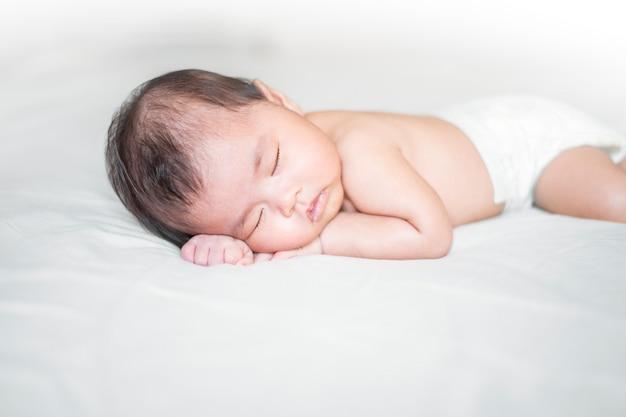 Lindo bebé recién nacido está durmiendo en la cama blanca Foto Premium