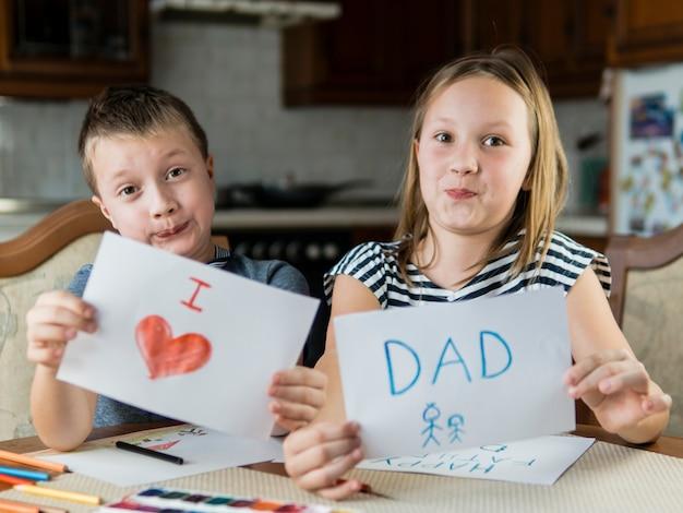 Lindo hermano y hermana dibujando para el día del padre Foto gratis