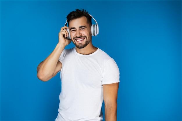 Lindo hombre europeo sonríe y escucha algo en los auriculares Foto gratis