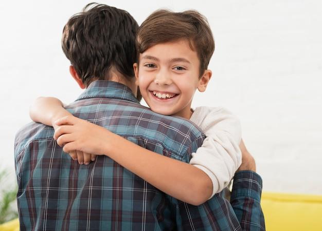 Lindo niño abrazando a su padre Foto gratis