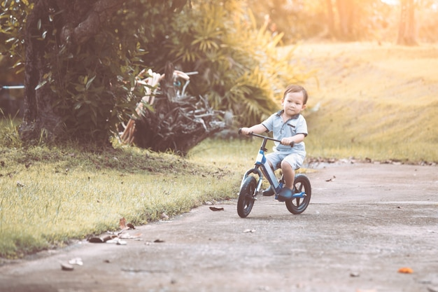 Niña Montando Su Bicicleta En Un Parque: Lindo Niño Asiático Niño Divirtiéndose Para Montar Su