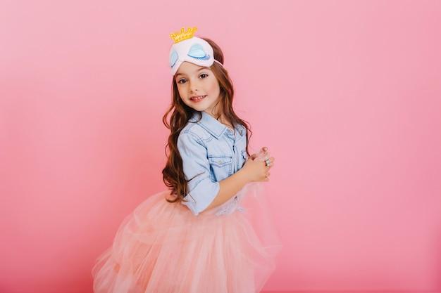 Lindo niño hermoso carnaval divirtiéndose aislado sobre fondo rosa. niña bonita con cabello largo morena, falda de tul, máscara de princesa expresando felicidad a la cámara, celebrando la fiesta de los niños Foto gratis