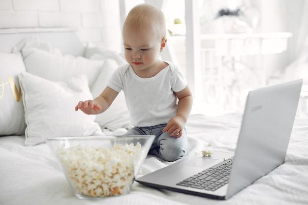 Lindo niño jugando con una computadora portátil en una cama Foto gratis