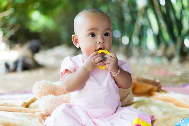 Lindo pequeño bebé asiático sentado y jugar con felicidad seleccionar foco poca profundidad de campo Foto Premium