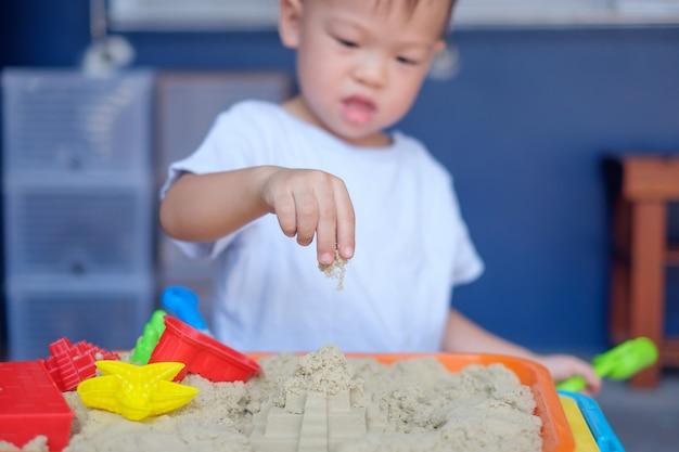 Un lindo y pequeño niño asiático de 2 años jugando con arena cinética en casa Foto Premium
