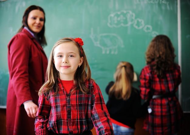 Lindos adorables escolares en el aula con actividades educativas Foto Premium