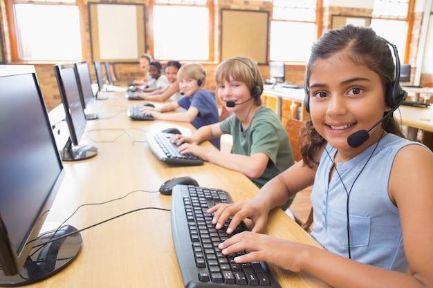 Lindos alumnos en clase de informática en la escuela primaria Foto Premium